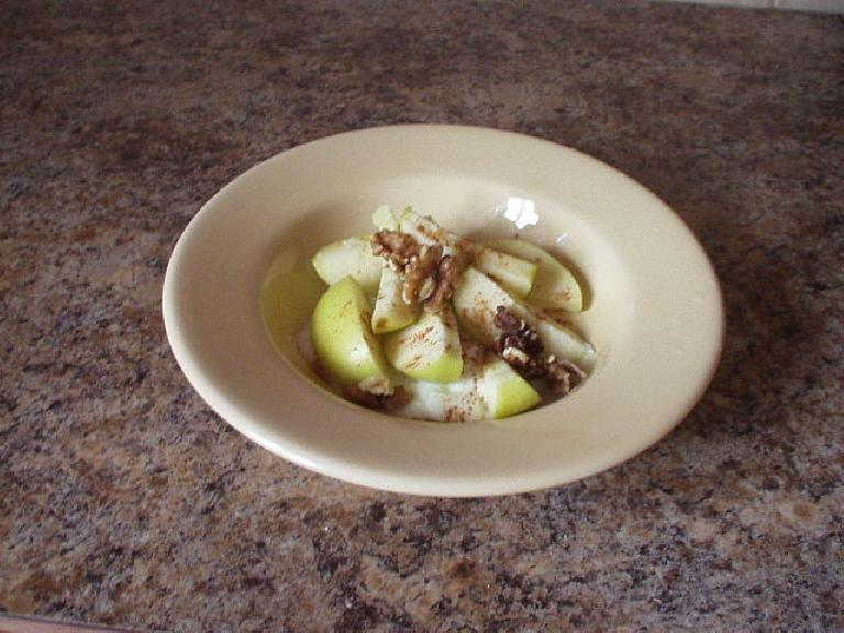 Green apples on mediterranean-style yogurt with walnuts and cinnamon.