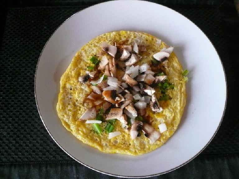Two eggs with white onions, green bell peppers, and mushrooms.