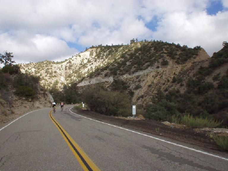 Mile 126, 4:05 p.m.: Cyclists riding out of the saddle.  See that diagonal horizontal ridge right above the midline of the picture?  We'd be going up that in just moments!