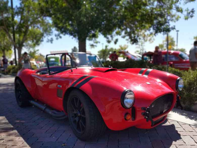 A red Shelby Cobra kit car with blacked-out chrome bits and matt black stripes.