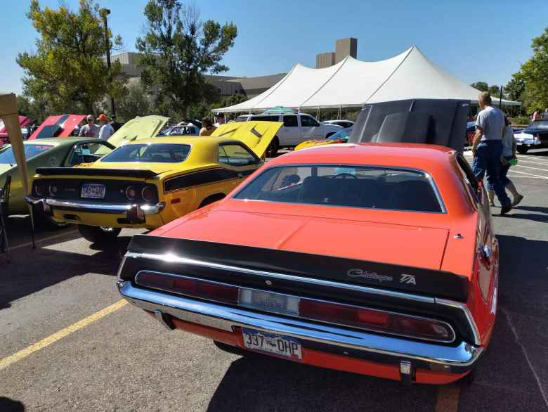 A yellow Plymouth Barracuda with an orange Dodge Challenger.