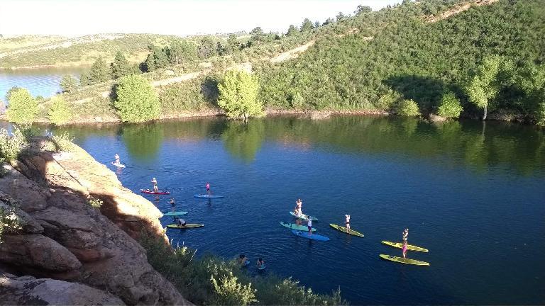 Yogis on paddleboards paddling back to Satanka Cove at Horsetooth Reservoir.