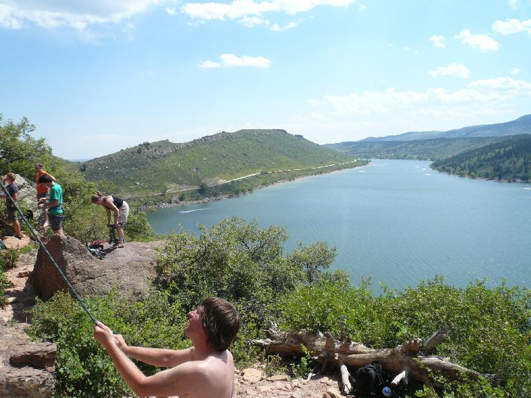 Derek belaying at Duncan Ridge with the Horestooth Reservoir behind.