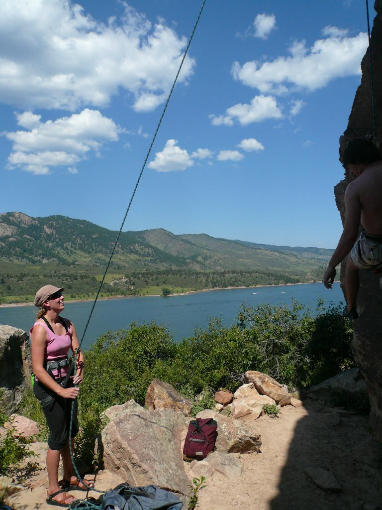 Anita belaying at Rotary Park with the Horsetooth Reservoir behind.