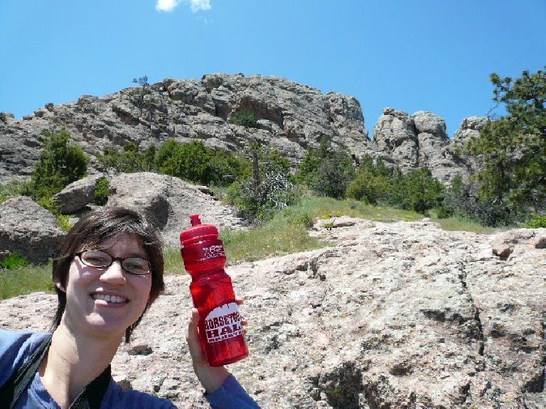 Sarah holding up a Horsetooth Half Marathon bottle which has a pretty accurate depiction of Horsetooth Rock.