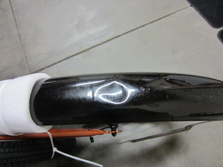 The rear fender had a large dent in it when I unpacked it.  The metal was thin, though, so I was able to push it back out with my fingers. (July 12, 2012)