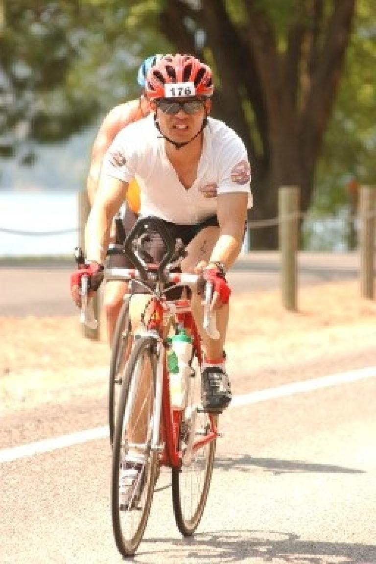 [Bike leg] Felix Wong passing another triathlete somewhere in downtown Coeur d'Alene. Photo: Action Sports International. (June 29, 2003)