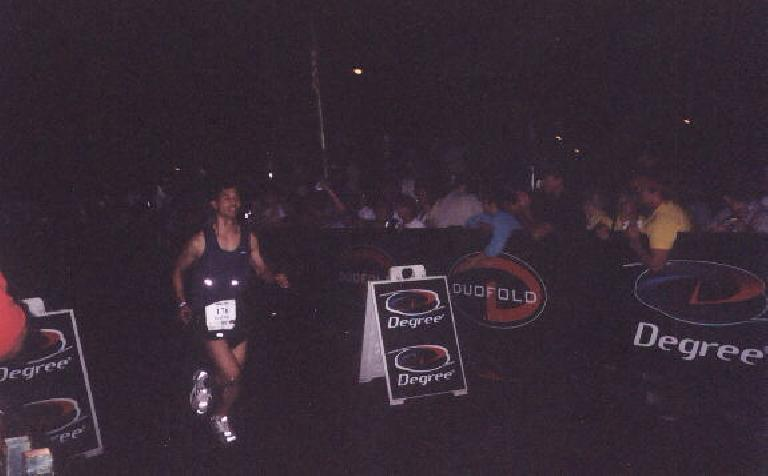 """Felix Wong coming down the finishing stretch giving high-fives to those in the stands while the announcer proclaimed, """"... and you are an IRONMAN!""""  What a feeling! Photo: Deborah Silva. (June 29, 2003)"""