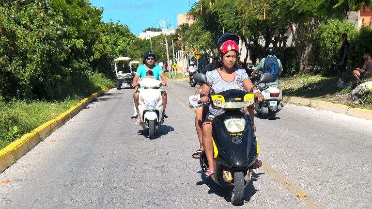 Mexicans driving motorbikes in Isla Mujeres.