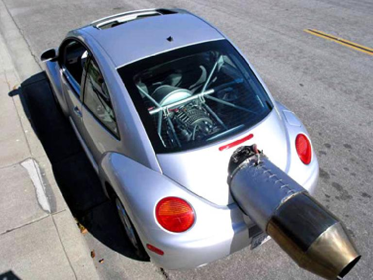 large jet engine sticking out of back of silver VN New Beetle.