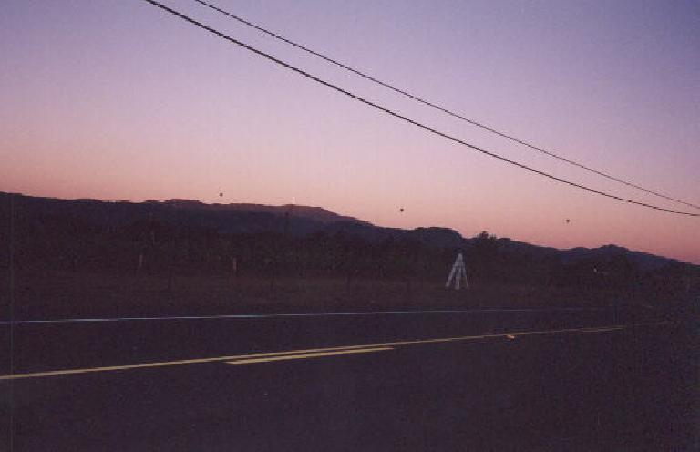 Balloons, wineries, and mountains lit by a pinkish sunrise.