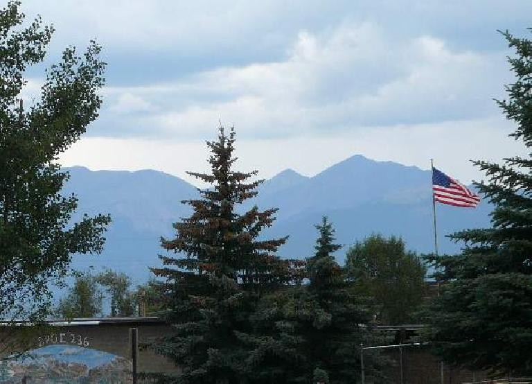 Flag waving in downtown Leadville with the mountains behind.