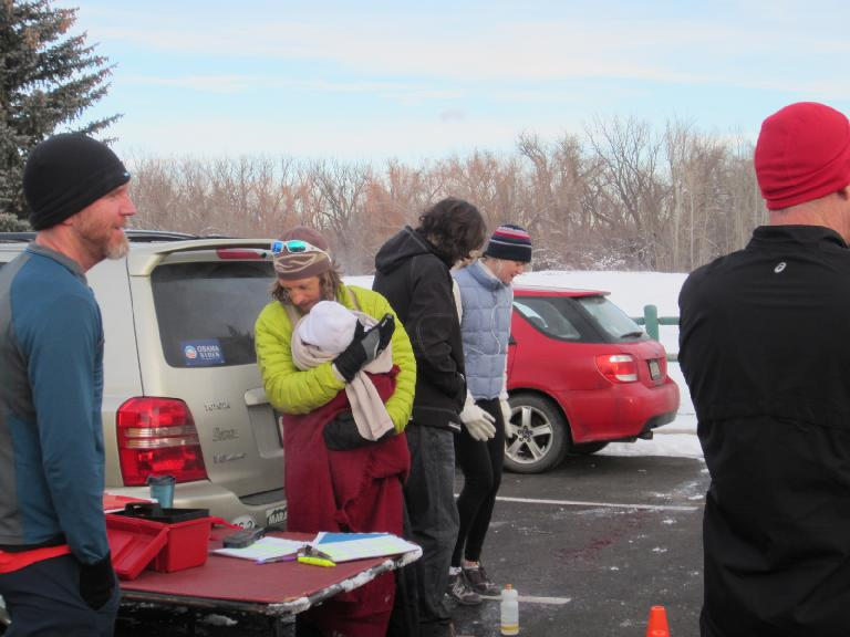 Race director Nick looking at the start times while keeping his newborn Stella warm.