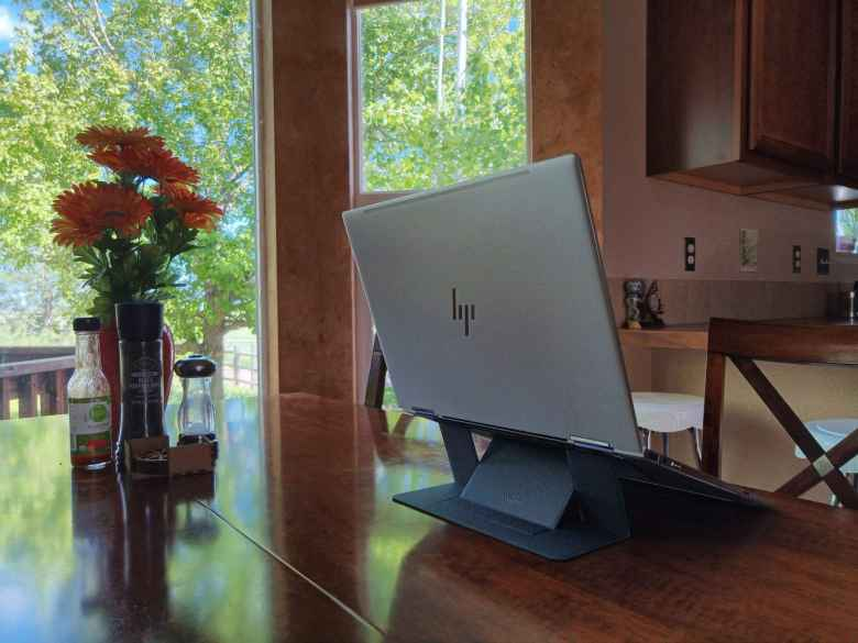 silver HP Spectre x360, black MOFT invisible laptop stand, table by windows