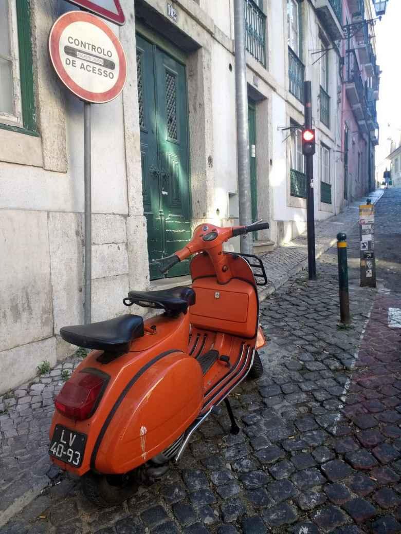 A vintage orange motorbike in Lisbon, Portugal.