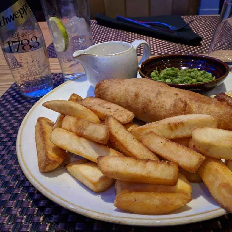 Fish and chips, peas, and tonic water at Roba Bar & Restaurant in London.