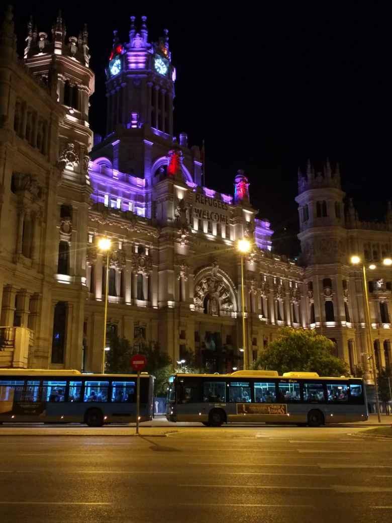 Buses in front of Palacio de Cibeles at night.