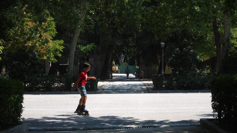 A boy skating through el Parque del Retiro.