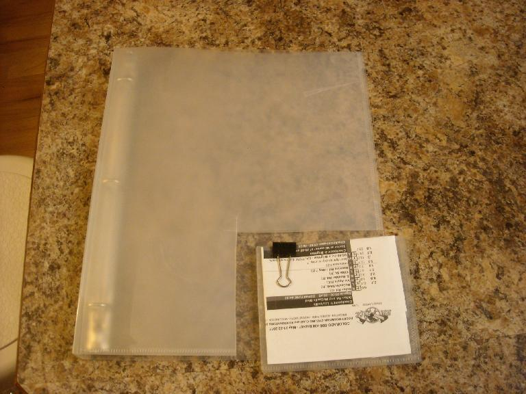 "Cutting down the binder to a more appropriate size (5 inches X 4 inches).  Two pieces of plastic are then joined together by clear tape to create a ""pocket."""