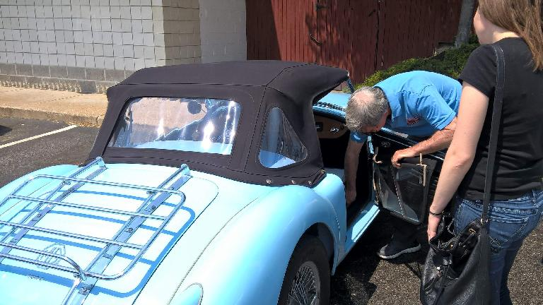 Mike Jacobsen shows Maureen the side curtains on his light blue MGA roadster.