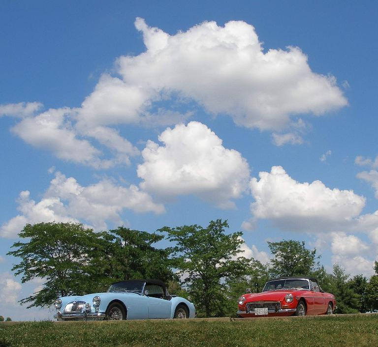 Mike Jacobsen's light blue MGA and Jennifer Orum's red 1970 MGB below some puffy clouds at the Wright City rest stop off I-70. Photo: Mike Jacobsen. (June 19, 2016)