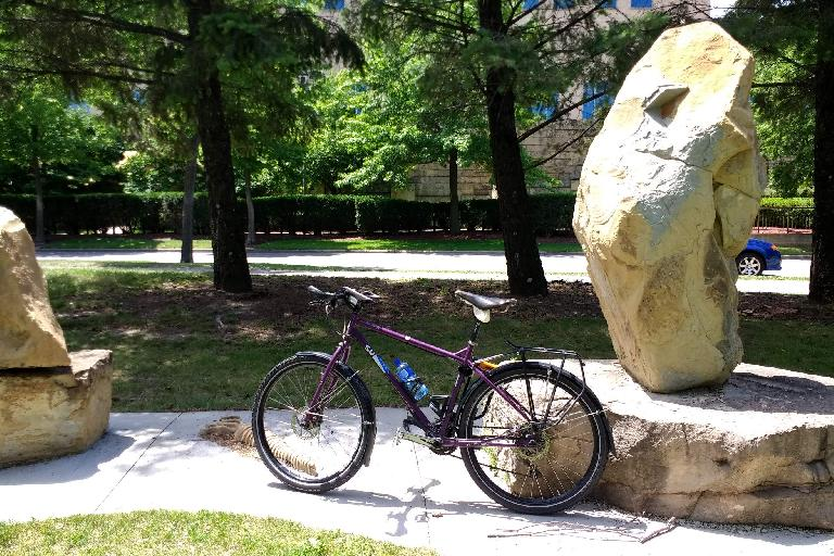 Dan's purple Surly in front of some stone art on the West Riverfront Parkway.