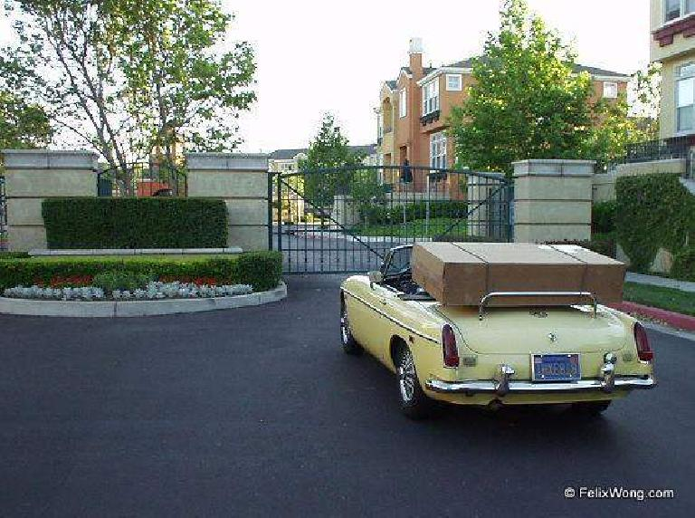 yellow MGB convertible, large cardboard box on luggage rack, bike box
