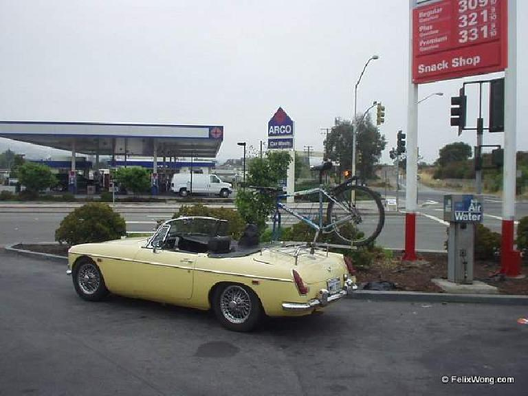 yellow MGB convertible, custom bike rack mounted to luggage rack, carrying blue mountain bike