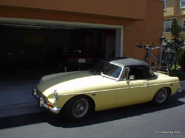 yellow MGB carrying blue mountain bike on custom bike rack, orange townhouse, garage