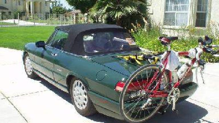 green 1991 Alfa Romeo Spider carrying red bicycle on bike rack