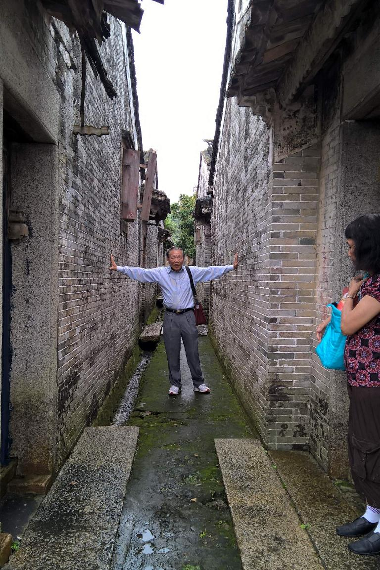 My dad showing the width between homes on a walkway near his childhood home.