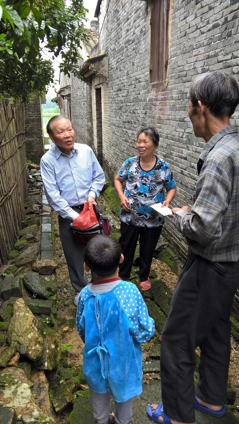 Some villagers heard us talking and came out to talk with us.  My dad gave them a gift.