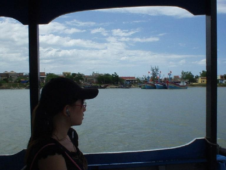 Vietnamese girl listens to MP3s on her Sony Ericson cell phone while looking out the boat from My Son to Hoi An.