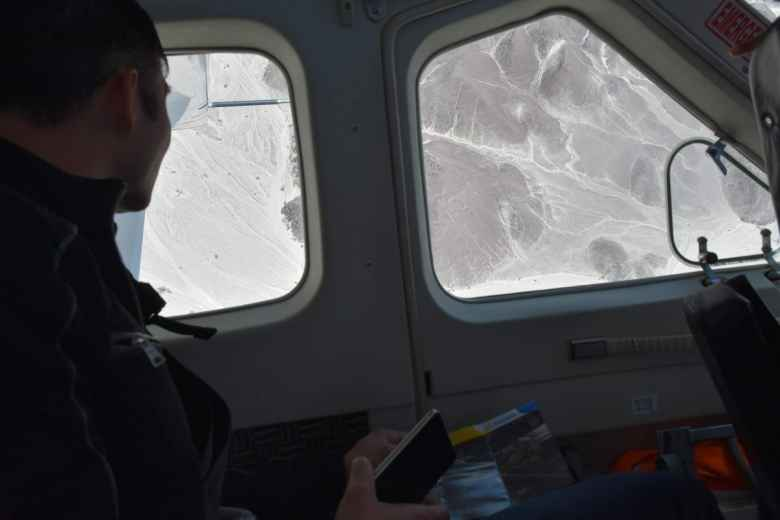 Felix Wong looking out the window of the airplane to view the Nazca Lines.