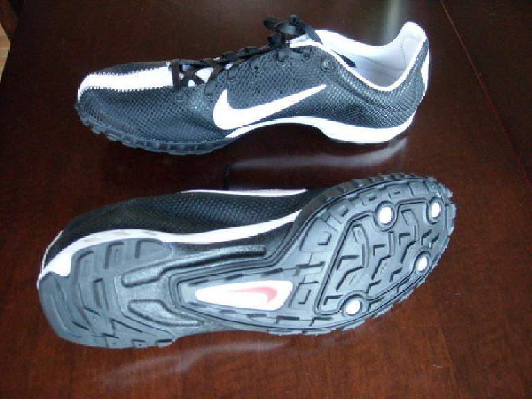 a pair of black and white Nike Zoom Waffle Racer VII shoes on a wooden table, with the sole of one visible