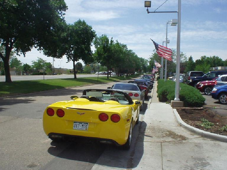 A row of All-American Corvettes with the star-spangled banner flying above.