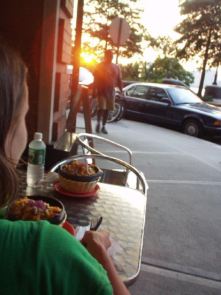 Carolyn with some delicious arroz con pollo in front of the waterfront while Felix Wong sneaks up behind her to snap this photo.
