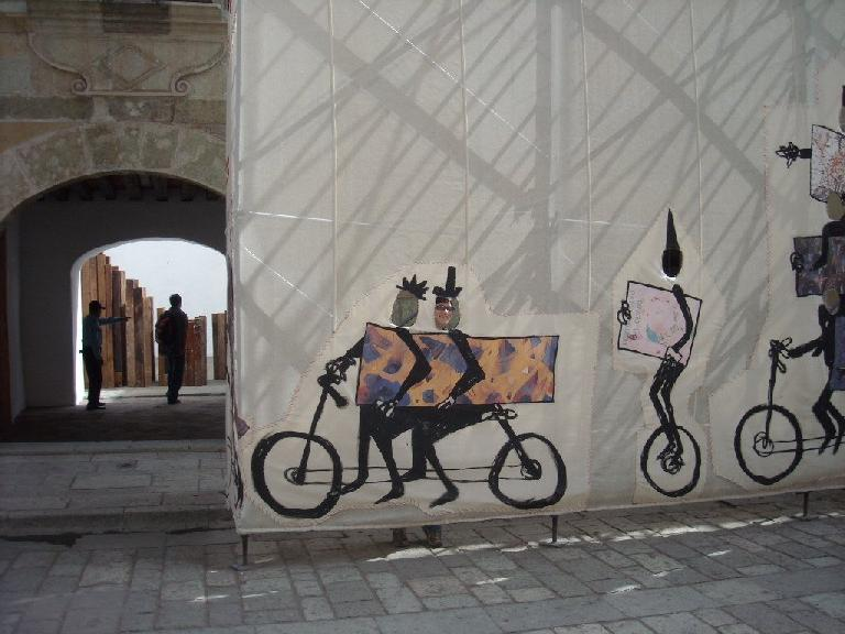 Sarah sticking her face in the hole of some bicycle art.
