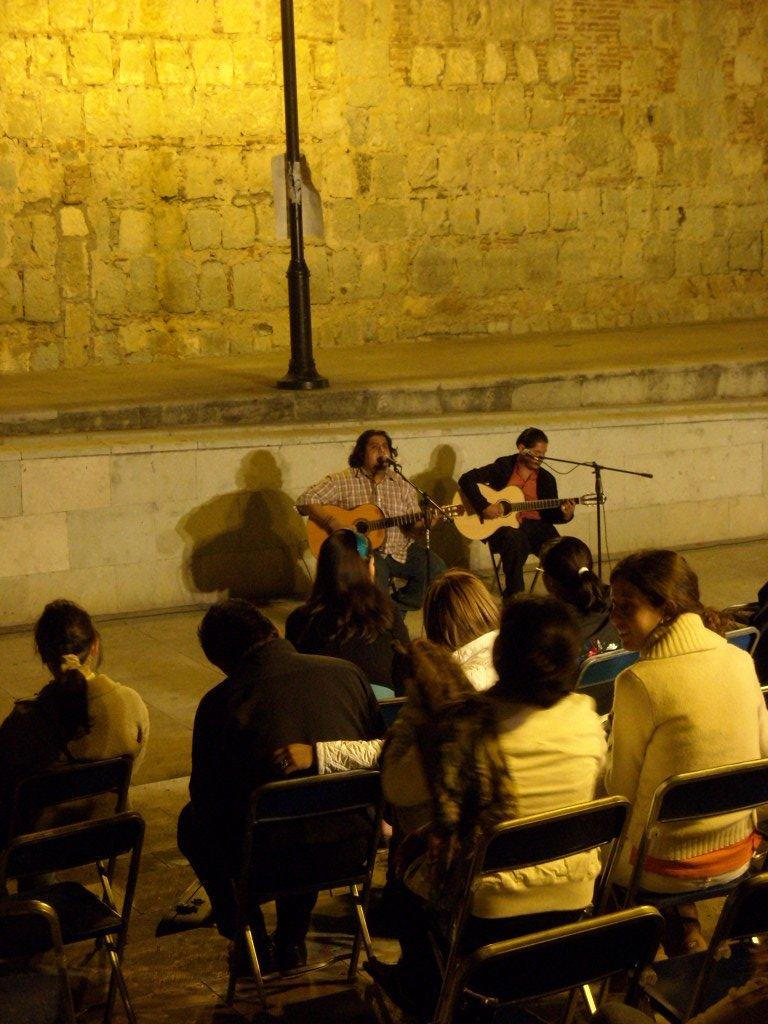 Two guys on acoustic guitars outside the Instituto de Artes Graficas in Oaxaca de Juarez.