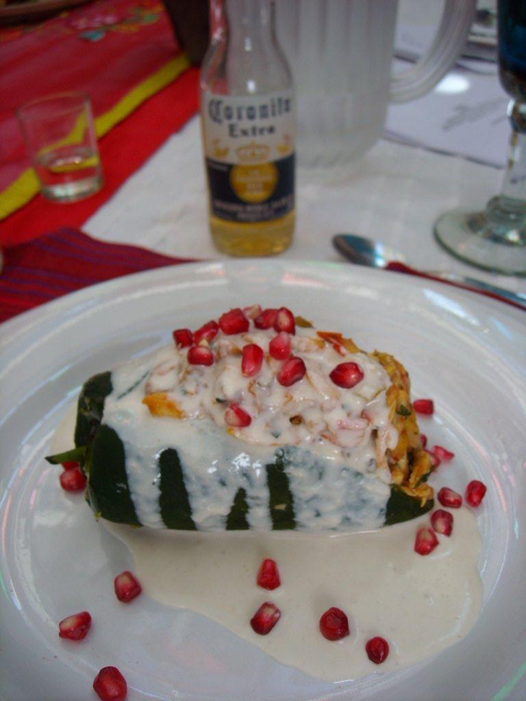 Chile de nogada with a cream and pomegranite seeds on top. The small bottle of Corona was labeled Coronita.