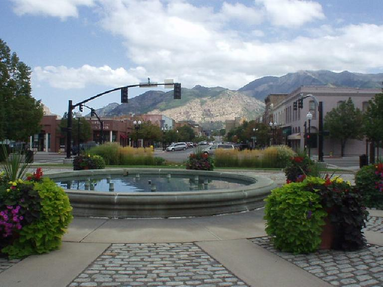 A fountain with downtown and the Wasatch Mountains in the background.
