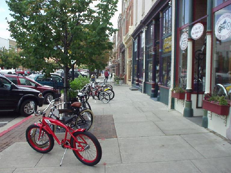 Bicycles downtown in front of a custom motorcycle shop.