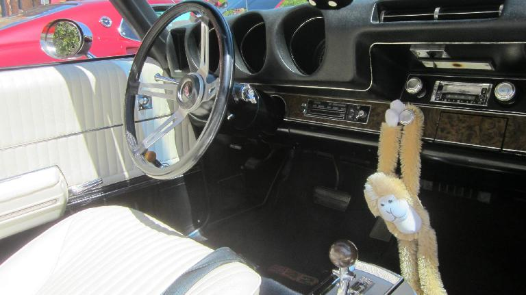 white interior of Oldsmobile 442 convertible, monkey hanging off knob