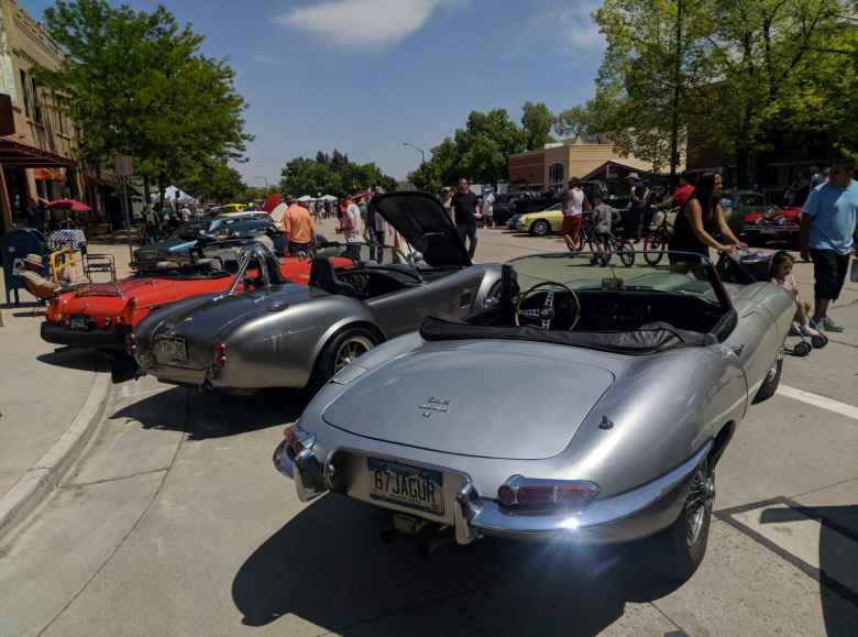 An orange-red MGB, silver AC Cobra (probably a replica), and and silver Jaguar E-Type convertible.