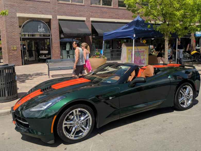 A green C6 Corvette Convertible with orange racing stripes.