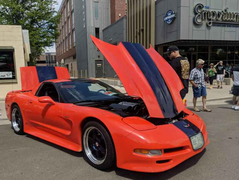 An orange C5 Corvette with black racing stripes.