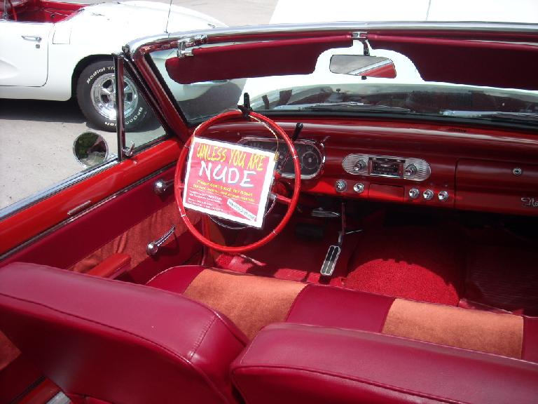 "The interior of a Chevy Nova convertible.  ""Don't touch unless you are NUDE"" proclaimed the sign."