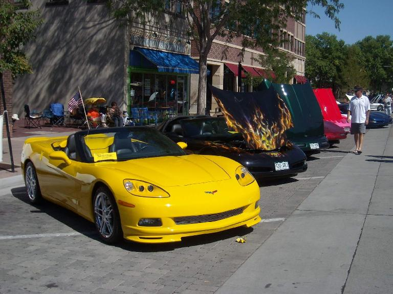 A line of modern Corvettes, including a yellow C6 convertible.