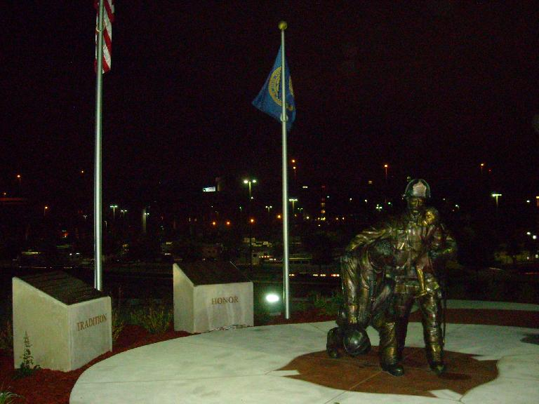 Statue near the Quest Center, with the lights of downtown Omaha beyond.