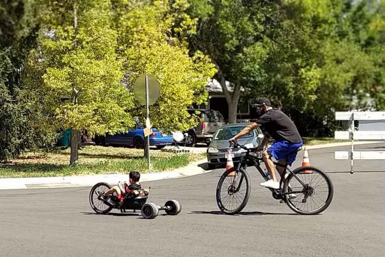 A boy riding a bicycle followed by a man riding a hardtail mountain bike.
